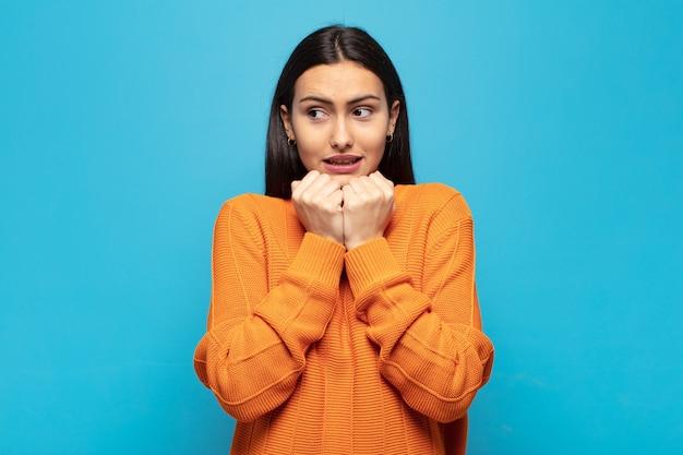 若いヒスパニック系の女性は、心配、不安、ストレス、恐れを見て、爪を噛み、横方向のコピースペースを探しています