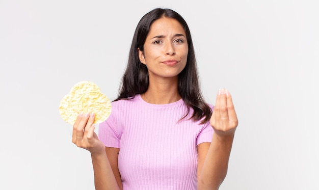 Young hispanic woman making capice or money gesture, telling you to pay and holding a rice cookie. diet concept