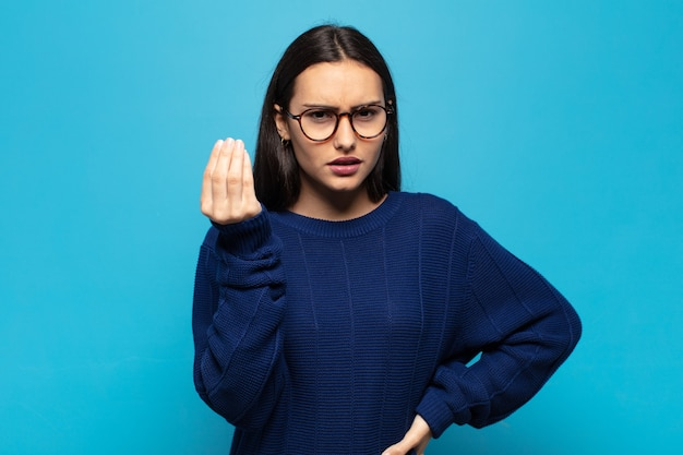 Young hispanic woman making capice or money gesture, telling you to pay your debts!