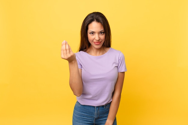 Young hispanic woman making capice or money gesture, telling you to pay