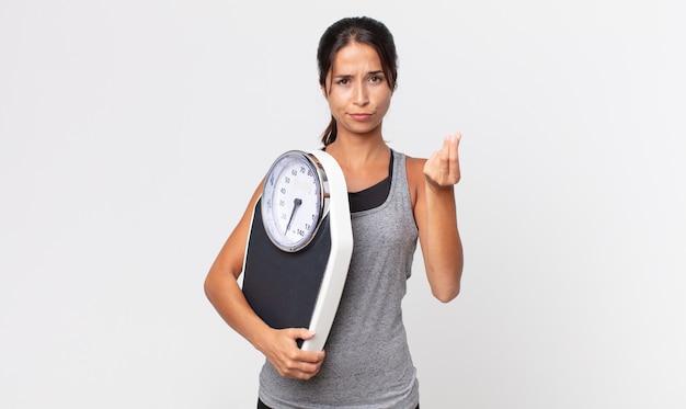 ヒスパニック系の若い女性が、体重計を持って支払うように言って、身振りやお金のジェスチャーをします。ダイエットコンセプト