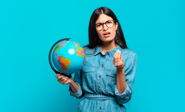 あなたの借金を支払うようにあなたに言って、capiceまたはお金のジェスチャーをしている若いヒスパニック系の女性!地球惑星の概念