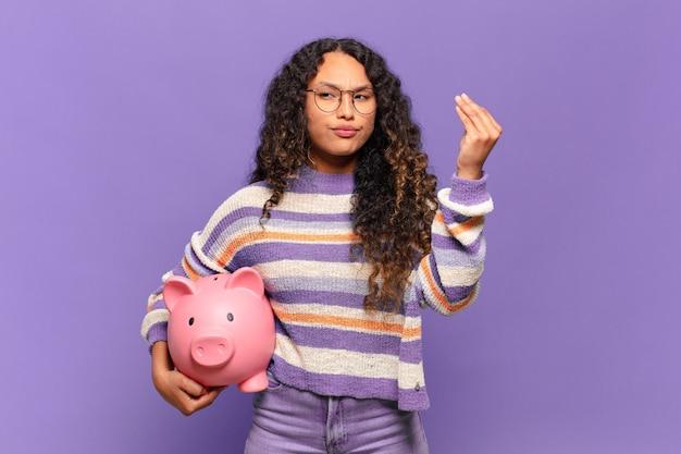 Молодая латиноамериканская женщина делает капризный или денежный жест, говоря вам, чтобы вы заплатили свои долги !. концепция копилки