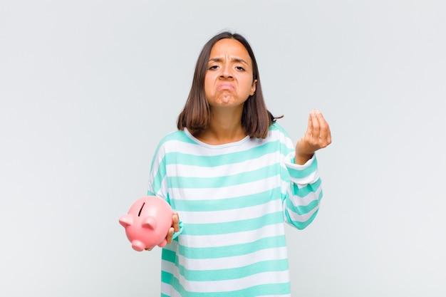 借金を返済するように言って、資本またはお金のジェスチャーをしている若いヒスパニック系女性!