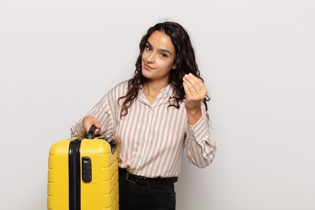 ヒスパニック系の若い女性が、借金を返済するように言って、身振りやお金のジェスチャーをしています!