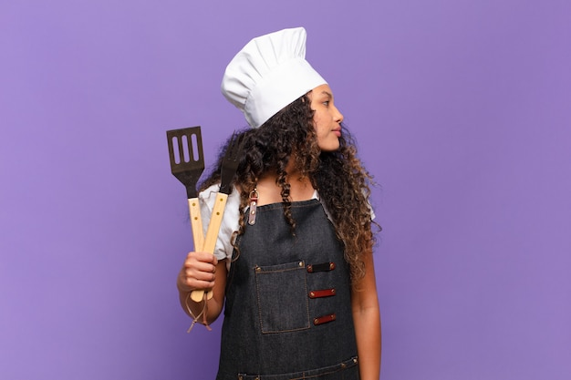Молодая латиноамериканская женщина на виде профиля, желающая скопировать пространство впереди, думать, воображать или мечтать. концепция шеф-повара барбекю
