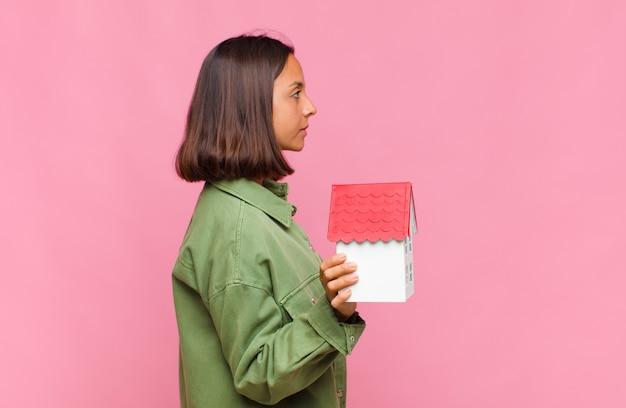 프로필보기에 젊은 히스패닉 여자, 생각, 상상 또는 공상 공간을 복사하기 위해 찾고