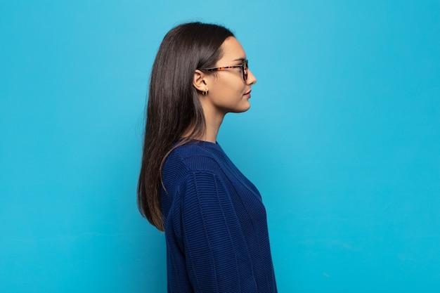 Молодая латиноамериканская женщина на виде профиля, желающая скопировать пространство впереди, думает, воображает или мечтает