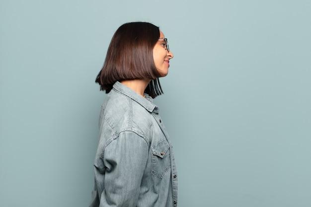 Молодая латиноамериканская женщина в профиле, стремящаяся скопировать пространство впереди, думает, воображает или мечтает