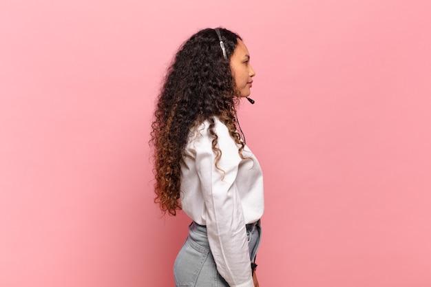 프로필 보기에 있는 젊은 히스패닉 여성은 앞서 공간을 복사하거나 생각하고 상상하거나 공상