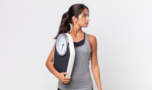 Молодая латиноамериканская женщина на представлении профиля думает, воображает или мечтает и держит весы. концепция диеты