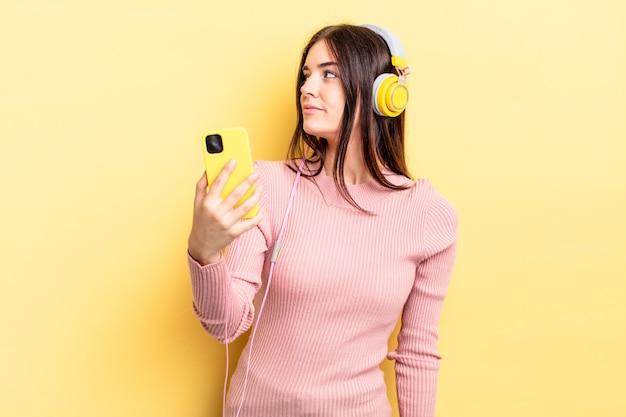 プロフィールビューの若いヒスパニック系の女性は、思考、想像、または空想にふけっています。ヘッドフォンと電話のコンセプト