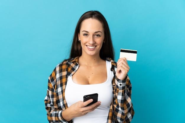 Молодая латиноамериканская женщина на изолированном синем фоне покупает с мобильного телефона с помощью кредитной карты