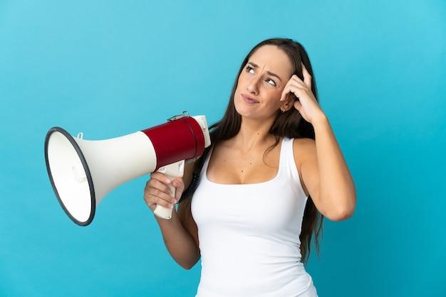 Молодая латиноамериканская женщина на изолированном синем фоне держит мегафон и сомневается