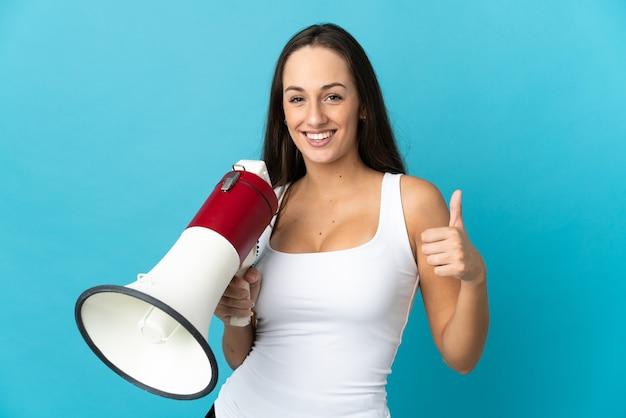 Молодая латиноамериканская женщина на изолированном синем фоне держит мегафон большим пальцем вверх