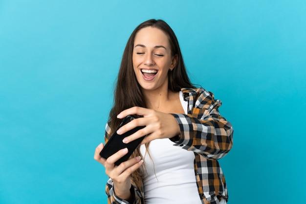 Молодая латиноамериканская женщина на изолированном синем фоне играет с мобильным телефоном