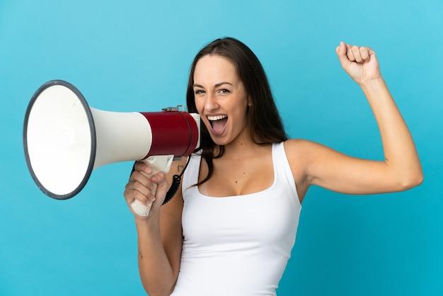 Молодая латиноамериканская женщина на изолированном синем фоне кричит в мегафон, чтобы что-то объявить