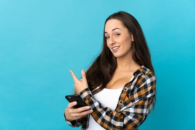 휴대 전화를 사용하고 다시 가리키는 격리 된 파란색 배경 위에 젊은 히스패닉 여자