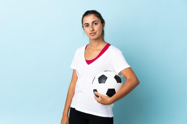 Молодая латиноамериканская женщина на изолированном синем фоне с футбольным мячом