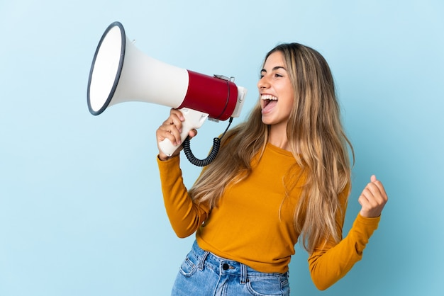Молодая латиноамериканка над изолированным синим криком в мегафон, чтобы объявить что-то в боковом положении