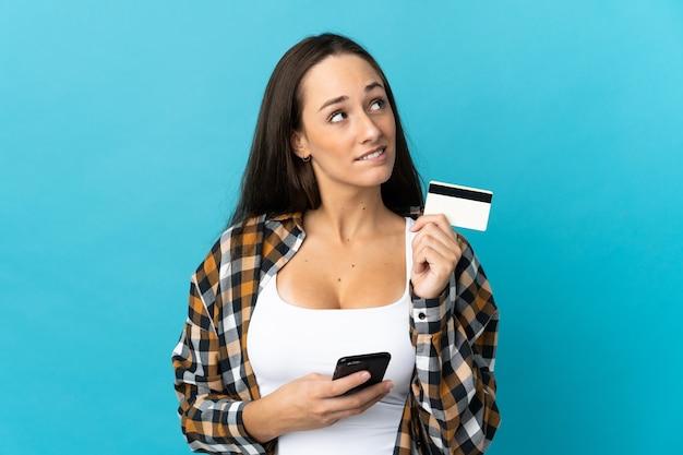 Молодая латиноамериканская женщина над изолированной синей стеной покупает мобильный телефон с помощью кредитной карты, думая