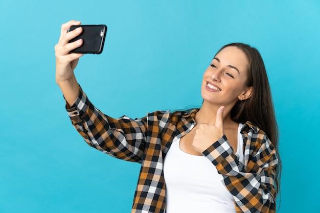 Молодая латиноамериканская женщина над изолированной синей стеной делает селфи с мобильным телефоном