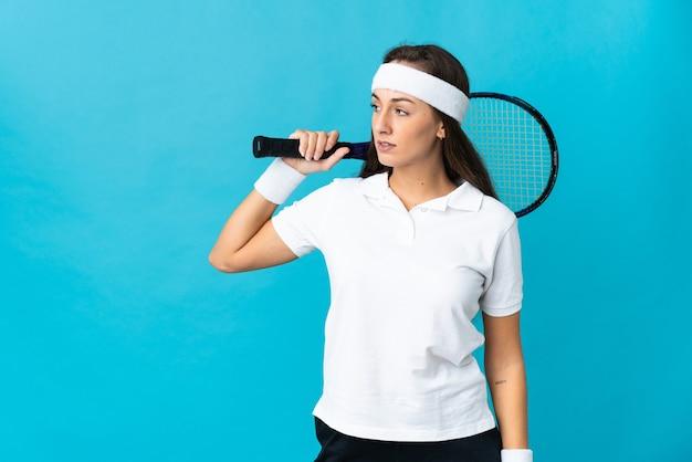 Молодая латиноамериканская женщина над изолированной синей стеной играет в теннис
