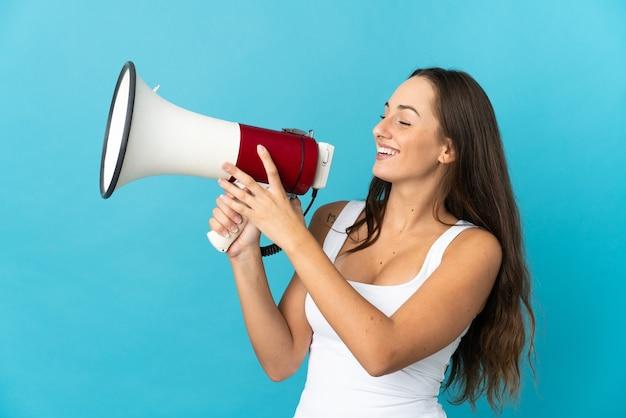 뭔가를 발표하기 위해 확성기를 통해 외치는 고립 된 파란색 벽 위에 젊은 히스패닉 여자