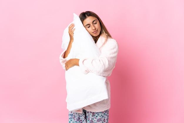 Молодая латиноамериканская женщина над изолированным розовым в пижаме и держит подушку во время сна