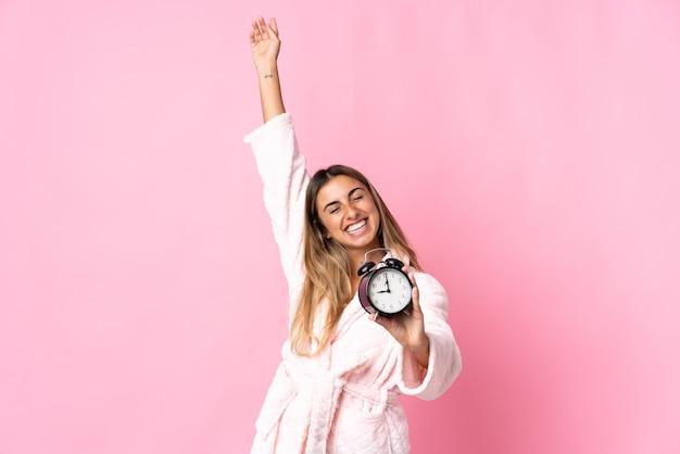 잠옷에 고립 된 분홍색 벽과 승리 제스처를 하 고 시계를 들고 젊은 히스패닉 여자