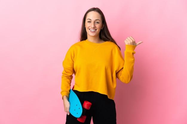 Молодая латиноамериканская женщина над изолированной розовой стеной с коньком и указывая в сторону