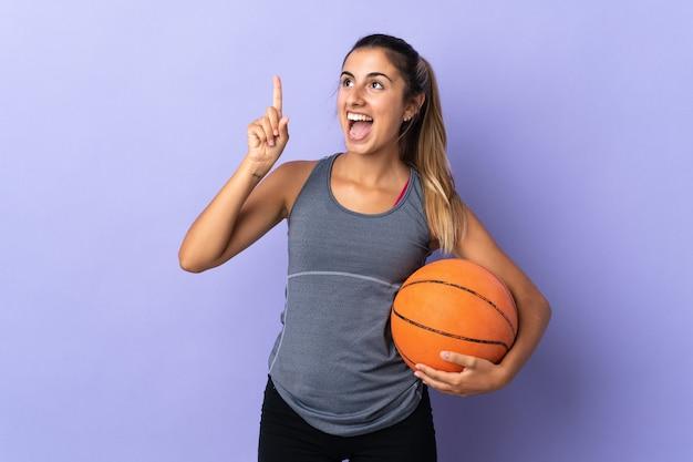 バスケットボールをしてアイデアを持っている孤立した紫色の壁の上の若いヒスパニック系女性