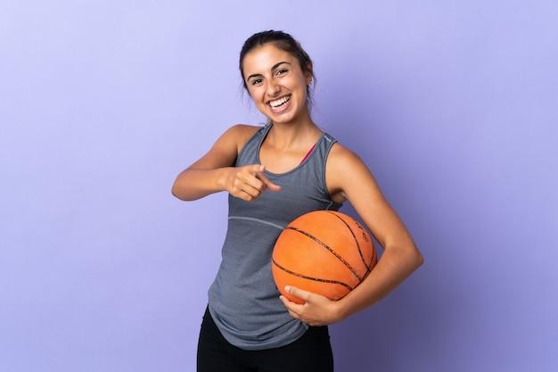 バスケットボールをし、正面を指している孤立した紫色の壁の上の若いヒスパニック系女性