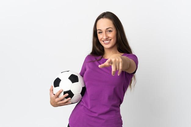 Молодая латиноамериканская женщина на изолированном белом фоне с футбольным мячом и указывая вперед