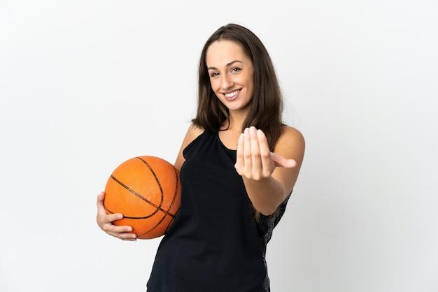 Молодая латиноамериканская женщина над изолированной белой стеной играет в баскетбол и делает приближающийся жест