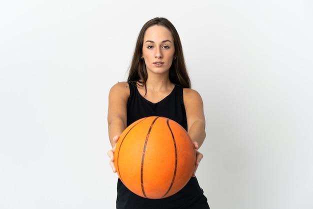 Молодая латиноамериканская женщина над изолированной белой стеной играет в баскетбол