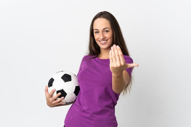 Молодая латиноамериканская женщина над изолированной белой стеной с футбольным мячом и делает приближающийся жест