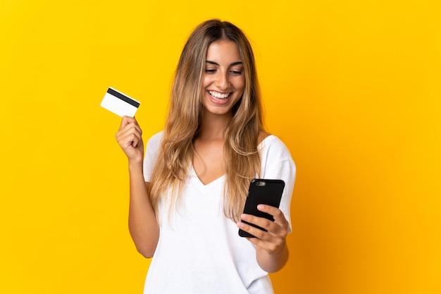 Молодая латиноамериканская женщина над изолированной желтой покупкой с мобильного телефона с помощью кредитной карты