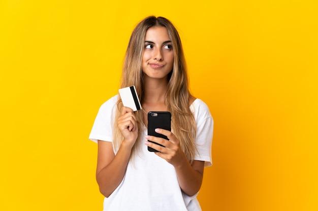 Молодая латиноамериканка над изолированной желтой стеной покупает мобильный телефон с помощью кредитной карты, думая