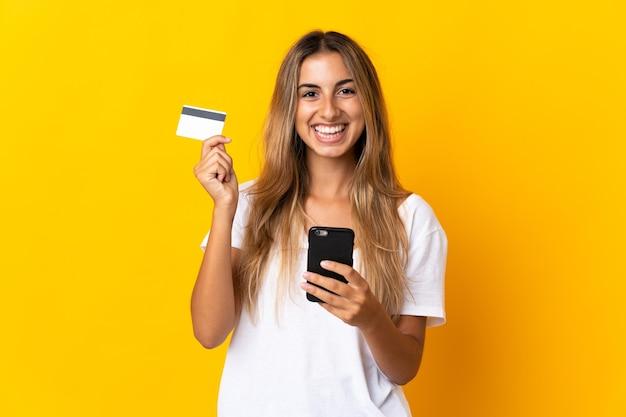 Молодая латиноамериканская женщина над изолированной желтой стеной покупает мобильный телефон с помощью кредитной карты