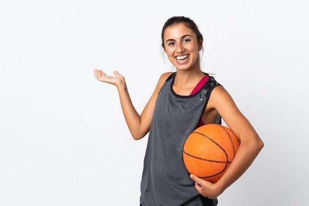 고립 된 흰색을 통해 농구를하는 젊은 히스패닉 여자와 서 초대를 위해 손을 옆으로 확장