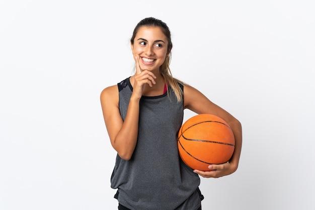 Молодая латиноамериканка играет в баскетбол над изолированной белой стеной, думая об идее, глядя вверх