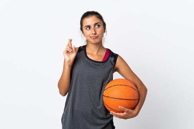 指が交差し、最高を願って孤立した白い壁の上でバスケットボールをしている若いヒスパニック系女性