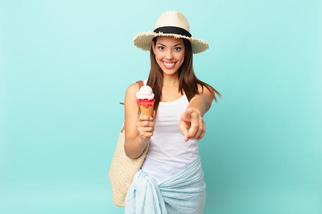 Молодая латиноамериканская женщина, указывая на камеру, выбирая вас и держа мороженое. концепция шумер