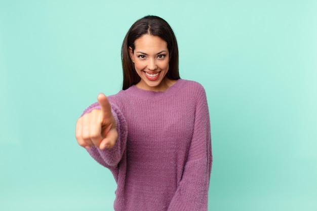 あなたを選ぶカメラを指している若いヒスパニック系女性