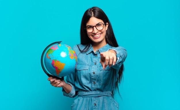 満足のいく、自信を持って、フレンドリーな笑顔でカメラを指して、あなたを選んでいる若いヒスパニック系女性。地球惑星の概念