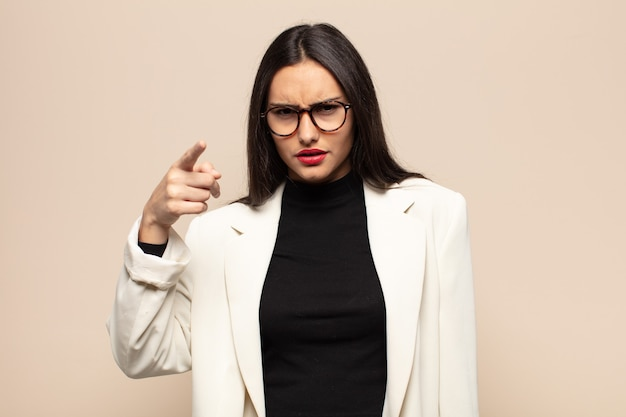 猛烈な、狂った上司のように見える怒っている攻撃的な表情でカメラを指している若いヒスパニック系女性