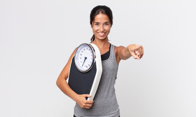 Young hispanic woman pointing at camera choosing you and holding a weight scale. diet concept