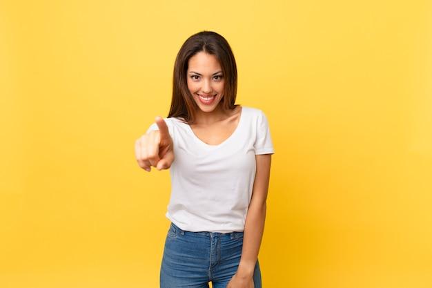 Young hispanic woman pointing at camera choosing you