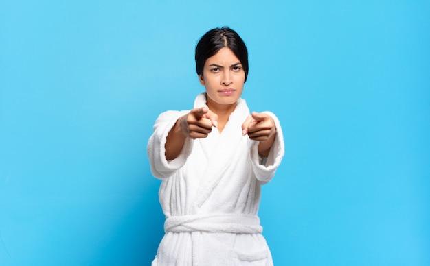 두 손가락과 화난 표정으로 카메라를 앞으로 가리키는 젊은 히스패닉 여자
